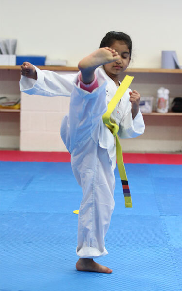 Junior Taekwondo student kicking